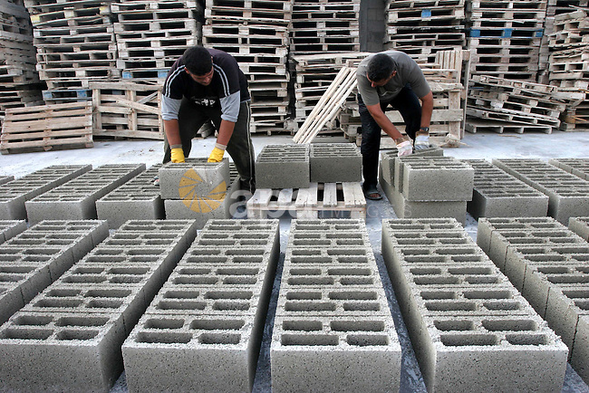 Palestinian workers make a blocks of stone at a stone factory in  Gaza city on July 20, 2009. the prices of stone block was raised from half US Dollar to one and half US dollar due to the closure of the crossings of the Gaza Strip and Israel does not allow the entry of construction materials, cement and wood and iron from the Gaza Strip crossings, and the Palestinian merchants are dependent on goods smuggled through tunnels under the land between Egypt and Gaza which cost high prices.  Photo by Mohammed Asad