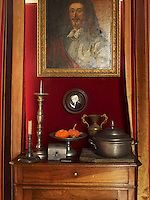A collection of pewter is displayed on a small side table beneath a gilt-framed portrait in the dining room