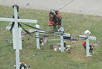 A miner photographs the memorial on the county courthouse lawn in Phillipi, WV Friday, Jan. 6, 2006, for four of the 12 miners killed in the Sago mine explosion. (Gary Gardiner/EyePush Newsphotos)<br />