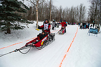 Laura Neese and team run past spectators on the bike/ski trail near University Lake with an Iditarider in the basket and a handler during the Anchorage, Alaska ceremonial start on Saturday, March 7 during the 2020 Iditarod race. Photo © 2020 by Ed Bennett/Bennett Images LLC