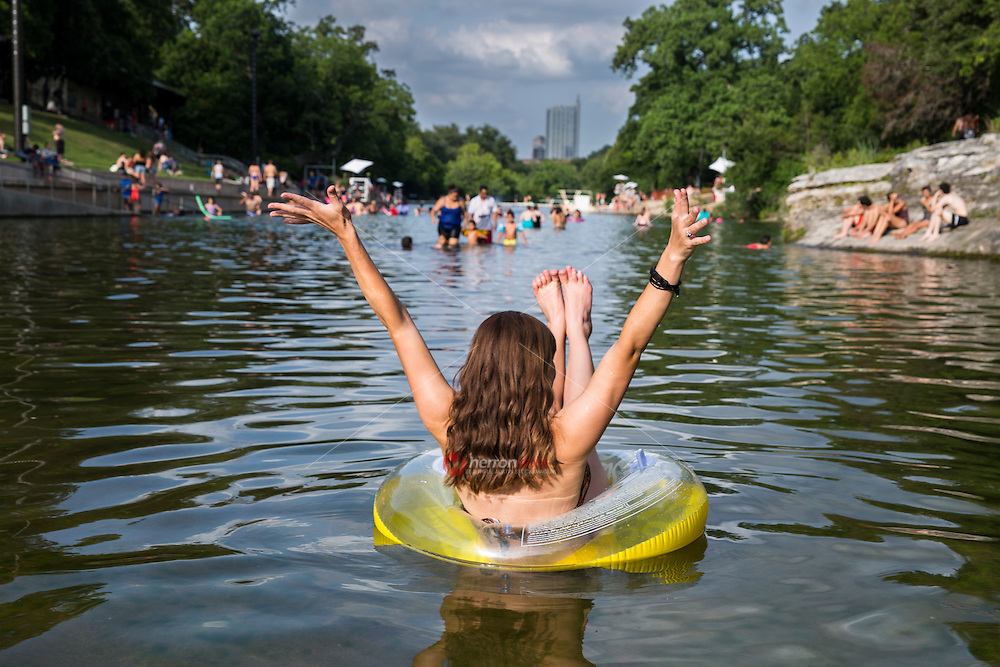 Backside of local Austin woman with arms outstretched in joy enjoying summer at Barton Springs Pool.