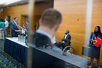 People mill about at the Recovering Warrior Employment Conference at the Back Bay Event Center in Boston, Massachusetts, USA. At center, seated, is Sherman Gillums, Deputy Executive Director of the organization Paralyzed Veterans of America. The employment conference was organized by Hiring Our Heroes and Wounded Warrior Project. Hiring Our Heroes is an initiative of the US Chamber of Commerce Foundation. Approximately 40 veterans registered for the event, during which they had interviews with a number of different regional and national employers, including GE, Bank of America, Uber, and others.
