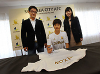Friday 02 November 2012<br /> Pictured: Footballer Ki Sung Yueng (C) and representatives from Nexon.<br /> Re: Sponsorship deal between Korean gaming firm Nexon and Swansea City FC at the Liberty Stadium, south Wales.