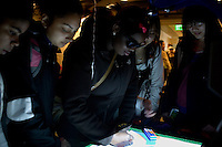 """Visitors play with """"The Neverending Drawing Machine,"""" a project by Edwina Portocarrero, research assistant in the Media Lab's Center for Future Storytelling, during the MIT Under the Dome open house in Cambridge, Massachusetts, USA."""