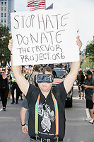 "Ryan Deame wears VR goggles and holds a sign reading ""Stop Hate / Donate / TheTrevorProject.org,"" as he marches in the Straight Pride Parade in Boston, Massachusetts, on Sat., August 31, 2019. The parade was organized in reaction to LGBTQ Pride month activities by an organization called Super Happy Fun America. The Trevor Project is an NGO focused on preventing suicide among LGBTQ youth."