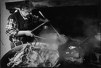 Europe/France/Midi-Pyrénées/12/Aveyron/Monteils: Jacky Carles cuit les carcasses au feu de bois dans un chaudron de cuivre
