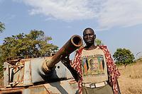 SOUTH SUDAN, Rumbek , SPLA soldier in T-Shirt with image of former SPLA leader John Garang in front of destroyed battle tank of North Sudanese army / SUED SUDAN Rumbek , SPLA Soldat vor einem zerstoerten Panzer der nordsudanesischen Armee , auf seinem T-Shirt ein Bildnis des 2005 bei einem Flugzeugabsturz umgekommenen Fuehres der SPLA , Suedsudanesische Volksbefreiungsarmee , John Garang , der Suedsudan strebt eine Unabhaengigkeit von Khartoum an
