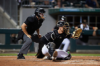 Charlotte Knights catcher Nate Nolan (28) sets a target as home plate umpire Jonathan Parra looks on during the game against the Norfolk Tides at Truist Field on August 19, 2021 in Charlotte, North Carolina. (Brian Westerholt/Four Seam Images)