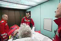 "Switzerland. Canton Ticino. Lugano. Ospedale Civico. In the lift on the way to the emergency room. The Rega has rescued an elderly man lying on a stretcher and suffering from a heart problem. Medical care. The pilot Corrado Sasselli (L), the emergency physician Michele Musiari (C) and the paramedic Paolo Menghetti (R). All Rega helicopters carry a crew of three: a pilot, an emergency physician, and a paramedic who is also trained to assist the pilot for radio communication, navigation, terrain/object avoidance, and winch operations. The name Rega was created by combining letters from the name ""Swiss Air Rescue Guard"" as it was written in German (Schweizerische Rettungsflugwacht), French (Garde Aérienne Suisse de Sauvetage), and Italian (Guardia Aerea Svizzera di Soccorso). Rega is a private, non-profit air rescue service that provides emergency medical assistance in Switzerland. Rega mainly assists with mountain rescues, though it will also operate in other terrains when needed, most notably during life-threatening emergencies. 10.09.2017 © 2017 Didier Ruef"