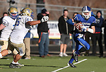 Carson's Joe Nelson scrambles from Reed defenders Cody Dehaan and Alden Giang during the NIAA D-1 Northern Regional title game at Bishop Manogue High School in Reno, Nev., on Saturday, Nov. 29, 2014. Reed won 28-25.<br /> Photo by Cathleen Allison