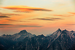 Lenticular clouds form during sunset over Golden Horn and Tower Mountain in Washington's North Cascade mountain range.