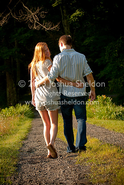 Young couple walking down driveway with arms around each other