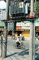 China. Province of Zhejiang. Hangzhou. China is facing a major crisis in energy due to the over  consumption  of electricity in the country. Electricity transformer station. A man rides his bicycle on the road while people are walking on the sidewalk.© 2004 Didier Ruef
