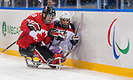 Sochi, RUSSIA - Mar 13 2014 - Billy Bridges checks Taylor Chace into the boards as Canada takes on USA in Sledge Hockey Semi-Final at the 2014 Paralympic Winter Games in Sochi, Russia.  (Photo: Matthew Murnaghan/Canadian Paralympic Committee)