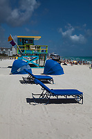 Blue Sunlounger Chairs, Sunshades and Lifeguard Tower, White Sand Tropical Beaches, South Beach, Miami, Florida, FL, America, USA.