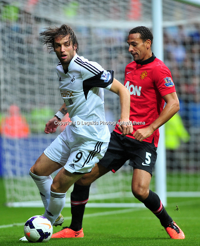 Swansea's Michu on the ball, Rio Ferdinand challenging.<br /> Saturday 17 August 2013<br /> Pictured: <br /> Re: Barclays Premier League Swansea City v Manchester United at the Liberty Stadium, Swansea, Wales