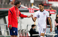 GUADALAJARA, MEXICO - MARCH 24: USA assistant coach Jeff Cassar congratulates Hassani Dotson #18 as he exits the field during a game between Mexico and USMNT U-23 at Estadio Jalisco on March 24, 2021 in Guadalajara, Mexico.