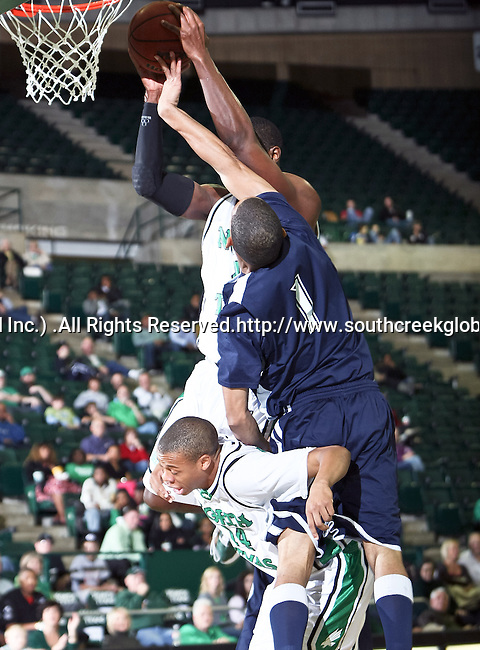 North Texas Mean Green forward George Odufuwa (4) goes up for a slam dunk over Jackson State University guard Cason Burke (1) knocking North Texas Mean Green guard Tristan Thompson (14) out of the way in the game between the Jackson State Tigers and the University of North Texas Mean Green at the North Texas Coliseum,the Super Pit, in Denton, Texas. UNT defeated Jackson 68 to 49