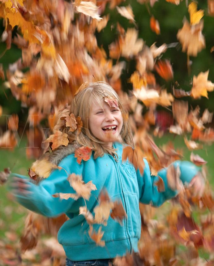 Girl under falling leaves lauging
