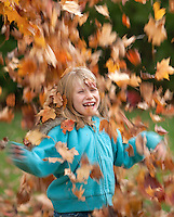 Girl under falling leaves lauging