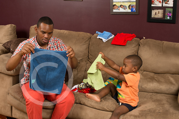 Three year old boy at home on couch with father household chores folding laundry