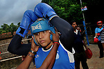 INDIA (West Bengal - Calcutta) August 2010,Shakila Babe prepairing herself before a bout during a practice in a local boxing club. Shakila and Shanno are twins from a poor muslim family of Iqbalpur, Kolkata. . Inspite of their late father's unwillingness to send his daughters to take up  boxing her mother Banno Begum inspired them to take up boxing at the age of 3. Their father was more concerned about the social stigma they have in their community regarding women coming into sports or doing anything which may show disrespect to the religious emotions of his community. Shakila now has been recognised as one of the best young woman boxers of the country after she won the  international championship at Turkey in the junior category. Shanno is also been called for the National camp this year. Presently Shakila and shanno has become the role model in the Iqbalpur area  and parents from muslim community of Iqbalpur have started showing interst in boxing. Iqbalpur is a poor muslim dominated area mostly covered with shanty town with all odds which comes along with poverty and lack of education. - Arindam Mukherjee