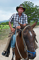 Trinidad Cuba cowboy on horse in country riding portrait in ranch with hat and chaps and cowboy clothes