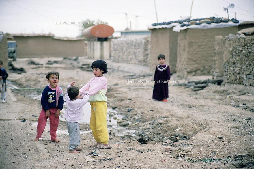 Irak 2000.Erbil: Des enfants de familles déplacées jouent dans les rues d'un ancien camp militaire irakien, lieu de leur résidence.     Iraq 2000.Children playing in a former Iraqi military camp