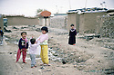 Irak 2000  Erbil: Des enfants de familles déplacées jouent dans les rues d'un ancien camp militaire irakien, lieu de leur résidence.     Iraq 2000 Children playing in a former Iraqi military camp