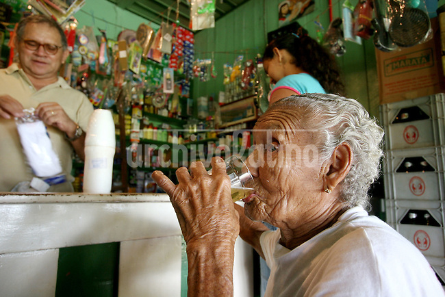 Olinda Pereira Branco, 95, drinks beers at a local shop in Fordlandia, a former factory town created by the Ford Motor Company on the banks of the Tapajós River, September 6, 2005. Branco, who worked as a nanny and maid for Ford executives, is one of the few residents who remember the Americans. Deep in the Amazon forest, 12 hours by boat from the regional capital of Santarem in Brazil's Pará state, the rubber plantation and processing factory is now abandoned to the rain-forest, an aging memorial to American ideals and to the Brazilian reality. It almost seems like time has stopped in Fordlandia, or better yet, time has passed it by. In typical american style, it was organized and efficient, an idea admired by many Brazilians, and perhaps more so by residents of the untamed Amazon. But It is an idea hard to implement in the wilds of the amazon. Some might also say that it is also a typical American style the way Ford came here and tried to implement something with little knowledge of the local customs or terrain. From 1928 to 1945, Ford came tried to take control of his rubber supply, one of the most important products of the rainforest. After only 17 years the company admitted defeat and retreated from the forest.
