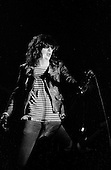 """Denver, Colorado<br /> USA<br /> May 9, 1983<br /> <br /> Front-man and Ramones singer: Joey Ramone in concert.<br /> <br /> The Ramones were an American rock band that formed in Forest Hills, Queens, New York in 1974, often cited as the first punk rock group. Despite achieving only limited commercial success, the band was a major influence on the punk rock movement both in the United States and the United Kingdom.<br /> <br /> All of the band members adopted pseudonyms ending with the surname """"Ramone"""", though none of them were actually related. They performed 2,263 concerts, touring virtually nonstop for 22 years. In 1996, after a tour with the Lollapalooza music festival, the band played a farewell show and disbanded.<br /> <br /> By a little more than eight years after the breakup, the band's three founding members--lead singer Joey Ramone, guitarist Johnny Ramone, and bassist Dee Dee Ramone--had all died."""