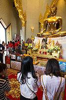Bangkok, Thailand.  Worshipers Pray before the Golden Buddha at the Wat Traimit Temple While Tourists Mingle in the Background.  The Buddha sits in the Bhumisparsha gesture, calling the earth to witness.