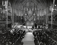 French Canada prays for victory in Notre Dame church; Montreal. Standing facing the sanctuary are his honor; Sir Eugene Fiset; lieutenant-governor of Quebec; and Lady Fiset. The church was filled by 5;000 worshippers<br /> <br /> [unknown]<br /> Picture, 1941<br /> <br /> PHOTO : Toronto Star Archives - AQP