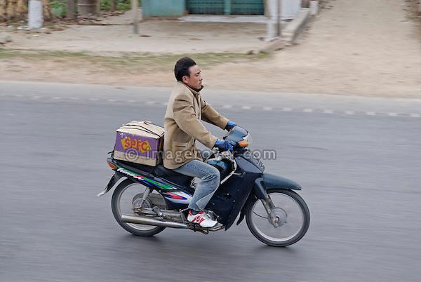 Asia, Vietnam, near Hue. Vietnamese man with some baggage on motorbike.