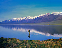 Fly fisherman on Mann Lake with the Steens Mountain, Oregon