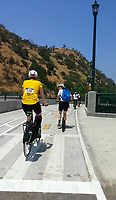 Holland, on his Yedoo Dragstr kick scooter, and Michelle, on her Terry Burlington city bike, chat as they ride up the Figueroa Street hill portion of the Los Angeles River Greenway Trail.   A few cyclists ride ahead of them, and a lovely California hillside is in the background.  . Taken during the 2017 (17th annual) Los Angeles River Ride.