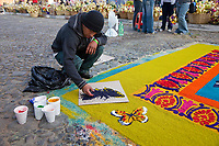 Antigua, Guatemala. Using a stencil to make a butterfly on an alfombra (carpet) of colored sawdust dedicated to nature.  The alfombra decorates the street in advance of the passage of a procession during Holy Week, La Semana Santa.