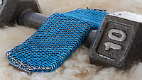 """A blue and silver dragonscale weave maille bracelet.  It's made from saw cut 18 gauge 1/4"""" ID blue anodized aluminum rings and saw cut 19 gauge 5/32"""" ID bright aluminum rings.  The clasp is a gunmental plated slide clasp.  The bracelet is on a sheepskin rug and a 10 pound dumbbell.   Handmade by Michelle."""
