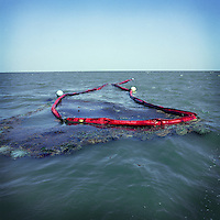 An oil slick marked and partially contained by hard boom and absorbent materials off the coast of Louisiana. After the Deepwater Horizon drilling platform explosion left a BP oil well spilling millions of gallons of oil leaked into the Gulf of Mexico, commercial fishing was banned leaving coastal residents largely unemployed. To help contain local anger and diffuse unemployment, BP attempted to hire local fishermen to help with the clean up.