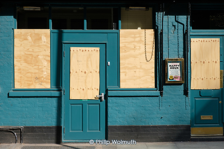Covid-19 pandemic lockdown. Happy Hour: closed and boarded up pub, Fitzrovia, London.