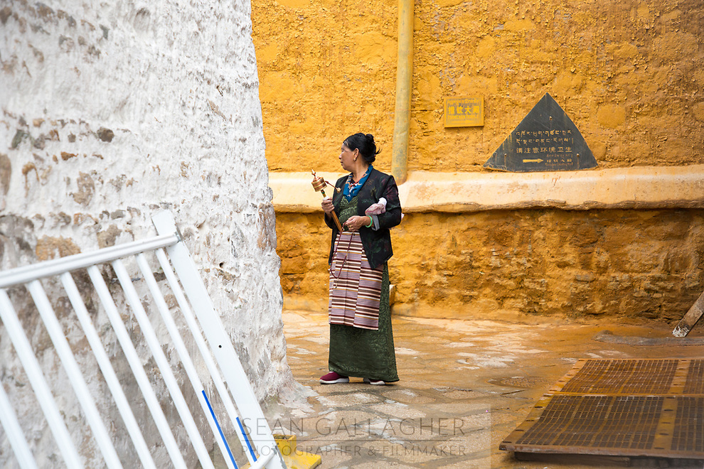 A pilgrim pauses as she walks through the narrow alleyways of Ganden monastery in Tibet. The monastery is one of the most important in the region and sits on top of a mountain near Lhasa at an altitude over approximately 4,300m.