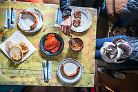 A ski tour through the Pirin Mountains of Bulgaria. A colorful table inside the Demianica Hut with traditional sausages and meatballs with peppers.
