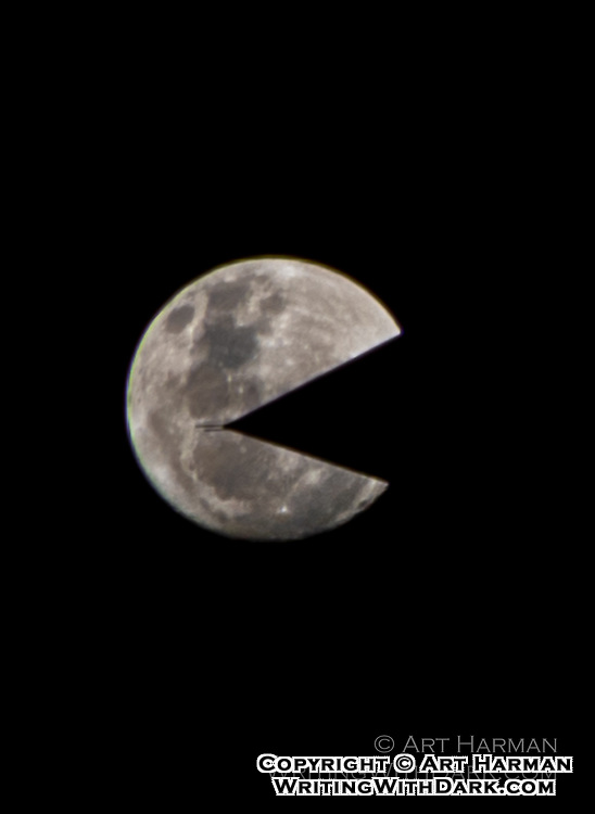 """Moon Pacman"" by Art Harman. While photographing the moon, it drifted over the Washington Monument. So I got a photo of the moon being impaled by the top of the monument. I turned it sideways, and suddenly the moon had a smiling face that looked like Pacman!"