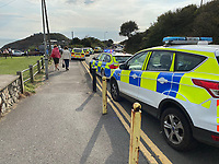 """Pictured: Emergency services at the scene of the incident in Bracelet Bay, near Swansea ales, UK.<br /> Re: A woman and her six-year-old daughter have been injured and taken to hospital after they were hit by a vehicle on a footpath in Bracelet Bay, near Swansea, Wales, UK.<br /> The unnamed young girl and her mother, 35, were hit by a car at a car park in Mumbles, Swansea.<br /> South Wales Police said a car had gone over an embankment and on to the path.<br /> Police confirmed her injuries were """"not life changing or life threatening"""".<br /> The 84 year-old driver of the car was not injured."""