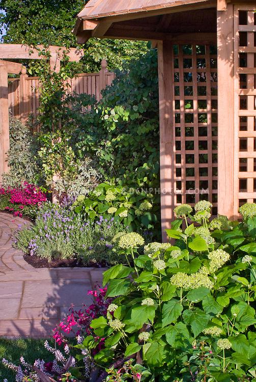 Garden gazebo building with hydrangeas, garden path and privacy wall, home landscape
