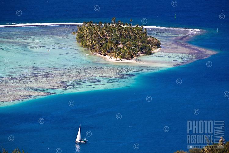 Yacht sailing into pass with sandy islet on Raiatea, Tahiti
