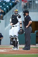 Charlotte Knights catcher Zack Collins (8) chats with home plate umpire Blake Carnahan during the game against the Buffalo Bisons at BB&T BallPark on July 24, 2019 in Charlotte, North Carolina. The Bisons defeated the Knights 8-4. (Brian Westerholt/Four Seam Images)