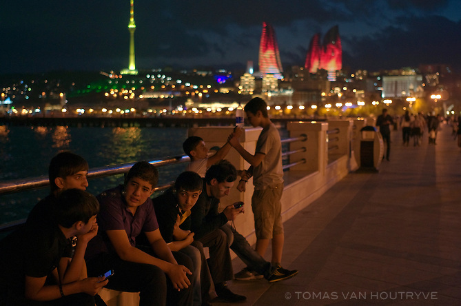 Youth gather on the seaside walkway known as Bulvar in Baku, Azerbaijan. In the background are newly built skyscrapers Flame Towers which are illuminated with flickering LED lights at night to resemble a massive fire.