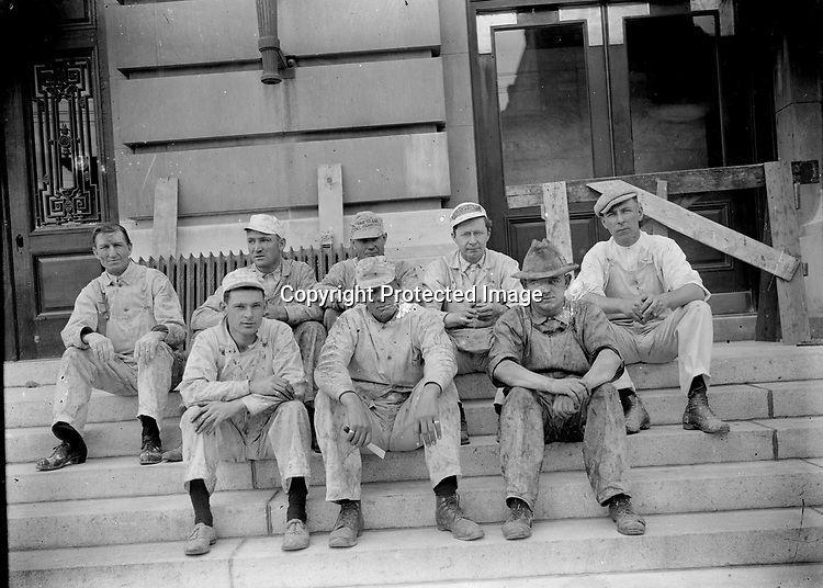 BUILDING CREW AT THE POST OFFICE, C. 1915. Eight workmen--probably painters--sit for a portrait on the east, main steps of the post office during the construction of 1915-1916. That project extended the original post office and rearranged much of the ground floor of the 1905 building. The lobby today retains marble wainscoting and oak trim from 1905, but in positions to which those fine finishes were relocated in 1915.<br /> <br /> Photographs taken on black and white glass negatives by African American photographer(s) John Johnson and Earl McWilliams from 1910 to 1925 in Lincoln, Nebraska. Douglas Keister has 280 5x7 glass negatives taken by these photographers. Larger scans available on request.