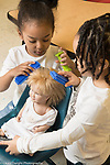 Education Preschool 4 year olds two girls pretend play beauty parlor working on doll's hair, using bristle blocks for combs and block for hairspray